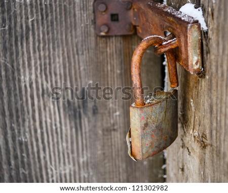 Old padlock on wooden door