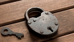 Old padlock with key on wooden background. Security concept
