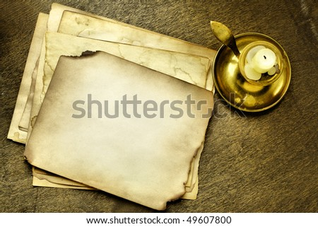 Old pages and candle on wooden table