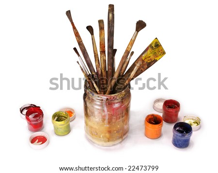 Old paint brushes in a glass jar with dried paint