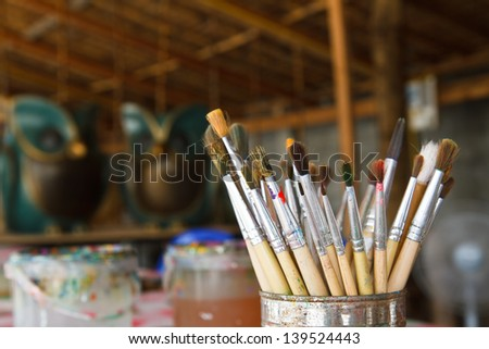 Old paint brushes in cans.