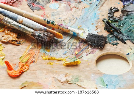 old paintbrushes on wooden used oils artistic pallette