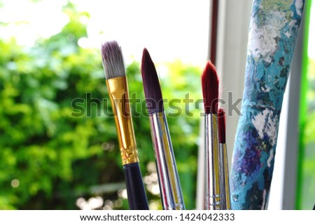 Old paintbrushes stained in the art for a long time. #1424042333