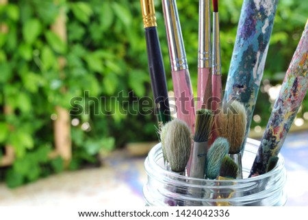 Old paintbrushes stained in the art for a long time. #1424042336