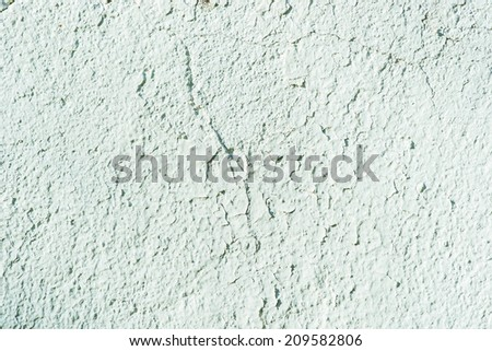 Old painted wall. Cracked paint of light green color. Grunge texture