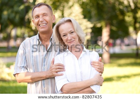 Old pair posing for camera in park