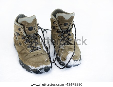 Old pairs of mountaineering boots on snow