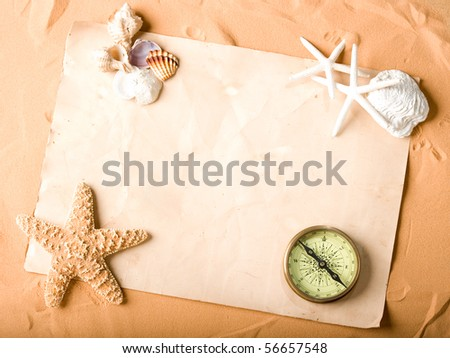 old paper and compass on sand background