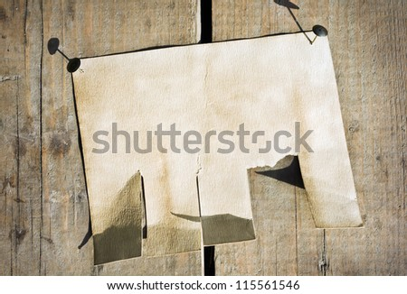 old paper announcement hanging on the wooden fence