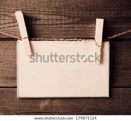 old paper attach to rope with clothes pins on wooden background