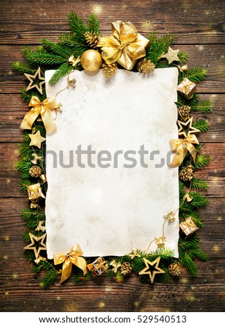 Old paper bordering with christmas decoration on wooden background #529540513