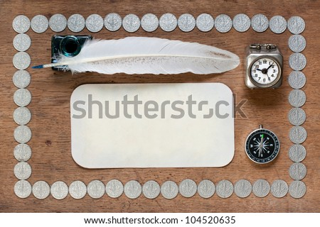 Old paper card, quill, inkwell, clock, compass on wood with antique silver coins background