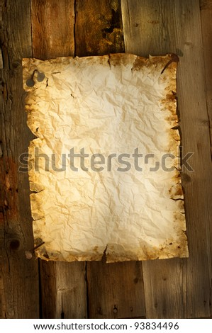 old paper clipped on wood background vertical
