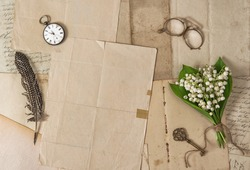 Old paper, feather pen, vintage accessories and spring flowers. Nostalgic background
