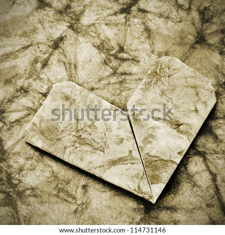 old paper heart in a background of textured old paper