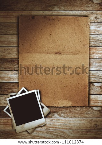 Old paper on with photo frame on wood background