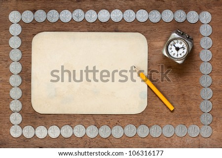 Old paper, pencil and clock on wood with antique silver coins frame