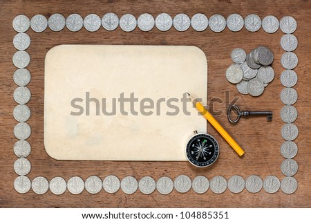 Old paper, pencil, compass and key on wood with antique Poland silver coins frame