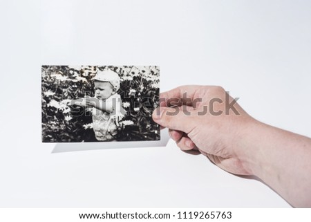 Old paper photo in mans hands. Abstract photo of childhood.