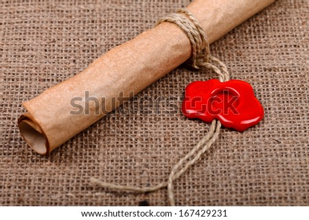 Old paper scroll with empty red wax seal on burlap background.