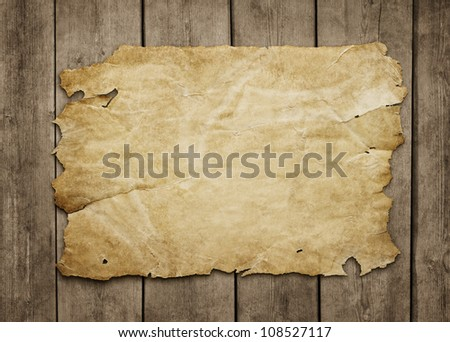 Old paper sheet at grunge wooden background with copy space