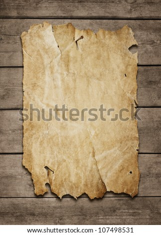 Old paper sheet nailed to a grunge wooden background with copy space