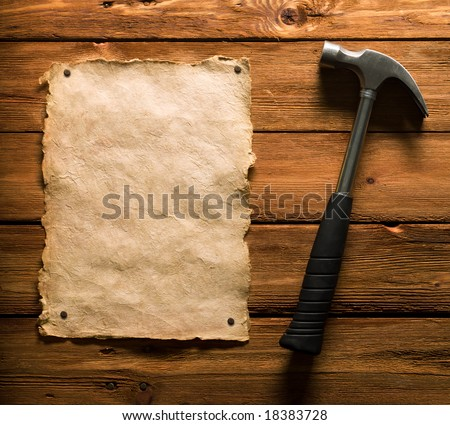 Old paper tacked to a wood board and hammer - stock photo