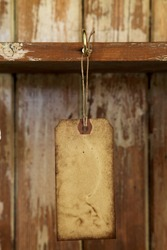 old paper tag with string hanged on on hook in old  wooden cupboard, shallow DOF