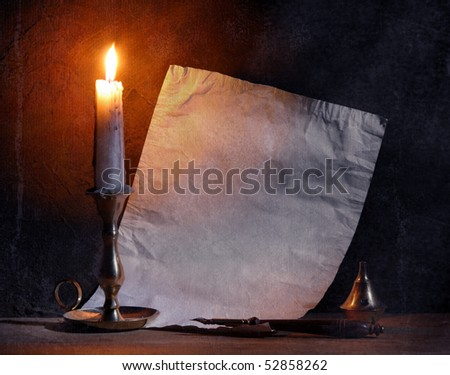 Old paper with a candle and a quill pen.