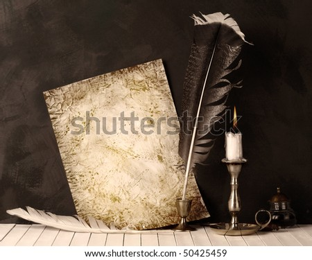 Old paper with a candle and a quill pen.Sepia