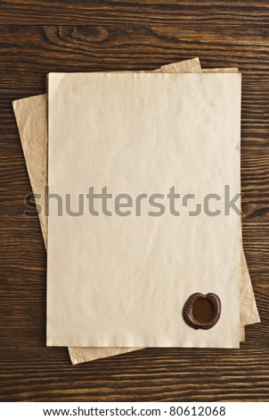 old paper with a wax seal on a wooden background