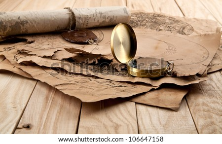 old papers and compass on wooden stome