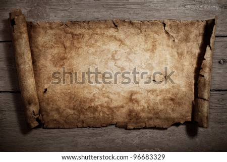 Old parchment on an old wooden background.Textured background - stock photo