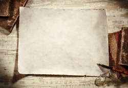 old parchment with books,spectacles and pen on antique writing desk
