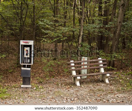 old pay phone booth and park bench in forest woods  #352487090