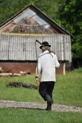 Old peasant carrying a scythe