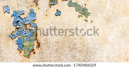 Old peeling paint on a vintage stucco wall. Cracked vintage paint in red, green and blue.                        Stock photo ©