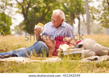 Old people, senior couple, elderly man and woman in park. Retired seniors eating food at picnic