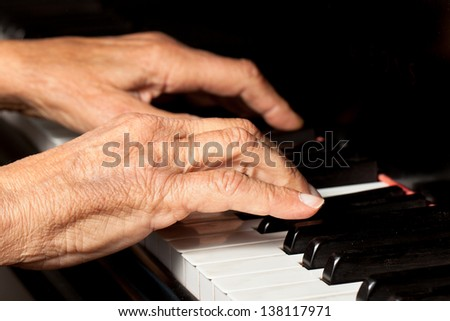 Old person\'s hands playing the piano. Close up view of skin texture and piano keys.