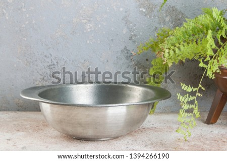 Old pewter bowl and green plant on a concrete background. Copy space for text. #1394266190