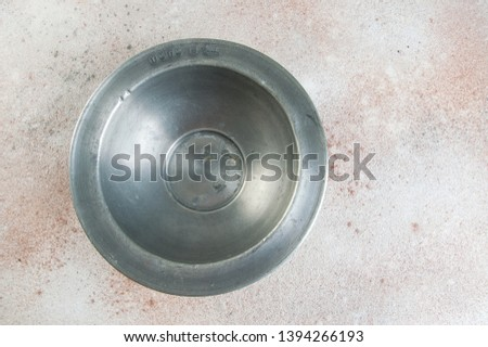 Old pewter bowl on a concrete background. Copy space for text. #1394266193