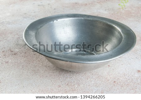 Old pewter bowl on a concrete background. Copy space for text. #1394266205