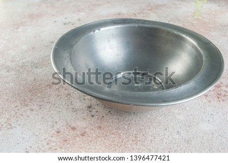 Old pewter bowl on a concrete background. Copy space for text. #1396477421
