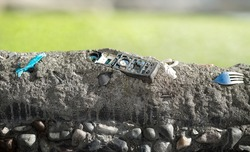 Old phone embedded in concrete layer with defocused landscape background. Human civilization garbage in sedimentation. Concept for human impact on planet earth and landfills. Selective focus.