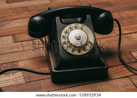 Old phone on the wooden parquet background #558933934