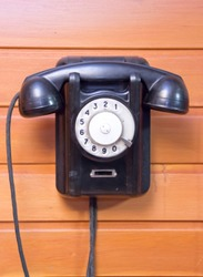 old phone with dialer disk on wooden background.