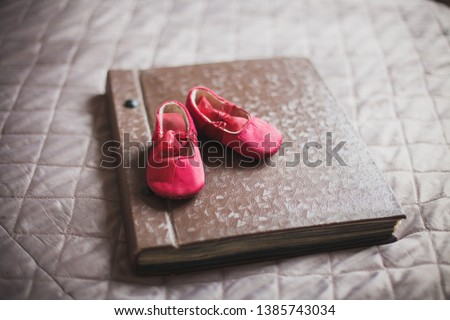 Old photo album. Brown photo album. On the photo album are pink shoes for a newborn girl. Memory. Family. Love. Childhood.