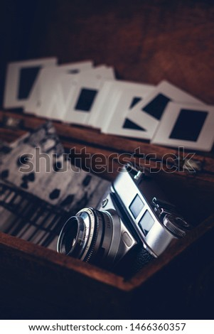 OLD PHOTO CAMERA IN WOODEN BOX NEXT TO BLACK AND WHITE PAPER PHOTOGRAPHY. VINTAGE PHOTOGRAPHY