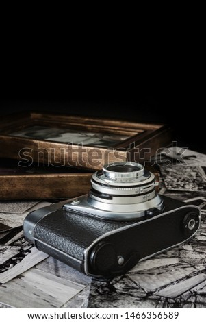 OLD PHOTO CAMERA WITH BLACK AND WHITE PHOTOGRAPHS AND WOODEN FRAMES. VINTAGE PHOTOGRAPHY