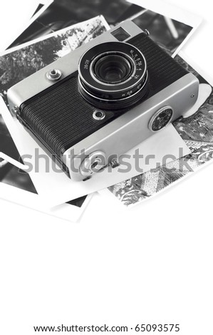 Old photo camera with photos on the white